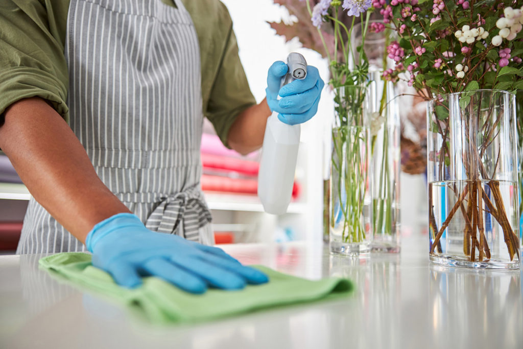 woman cleaning surfaces wearing latex gloves with flowers beside her | cleaning tips for hay fever sufferers shark vacuum