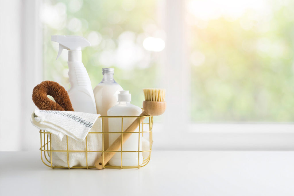 eco friendly cleaning products in a basket in front of a window | shark vacuum spring cleaning checklist