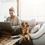 Woman sat working from a laptop on a sofa with her dog sat closely next to her | shark vacuum spring cleaning tips for homes with pets