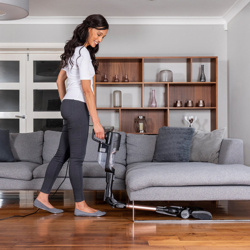 Woman vacuuming under her sofa using Shark corded upright HZ500UKT flexology | top tips to maintain your shark vacuum