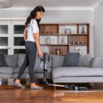Woman vacuuming under her sofa using Shark corded upright HZ500UKT flexology | top tips to maintain your shark vacuum