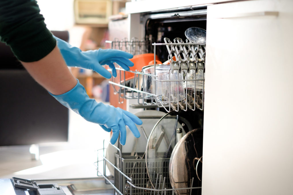 Woman opening dishwasher wearing rubber gloves | Shark vacuums UK | How to clean dishwasher tips