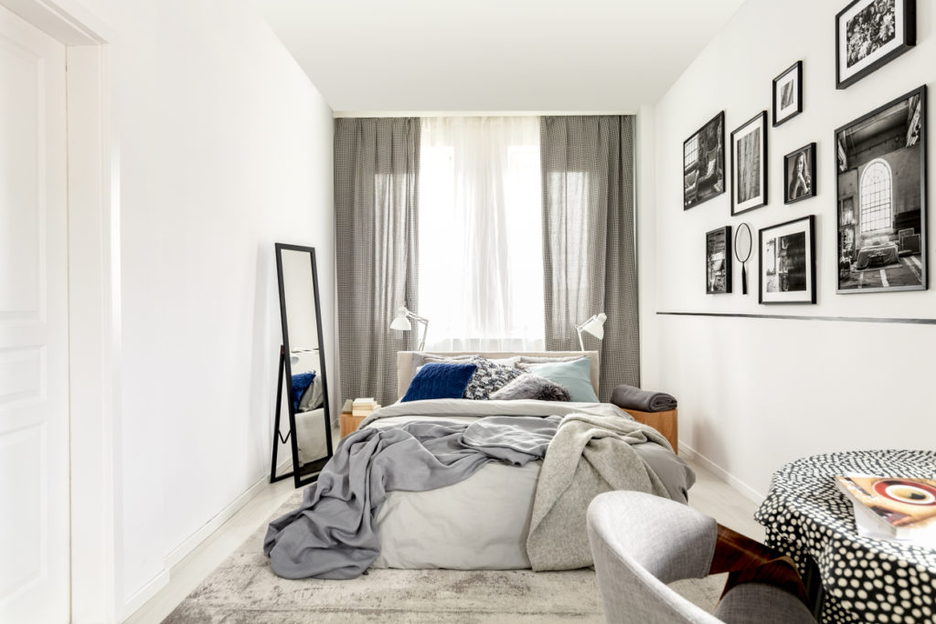 Image of a small bedroom with floor-to-ceiling windows behind the bed. Tips for how to clean your rental home before leaving. Shark clean UK vacuums